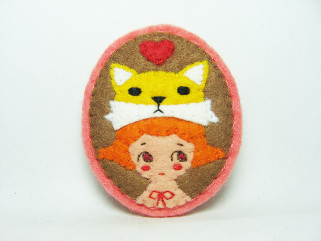 A girl with a yellow fox hat felt brooch
