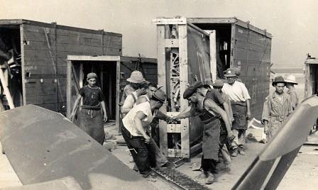 Varios hombres desembalan un Spitfire de su cajón de transporte