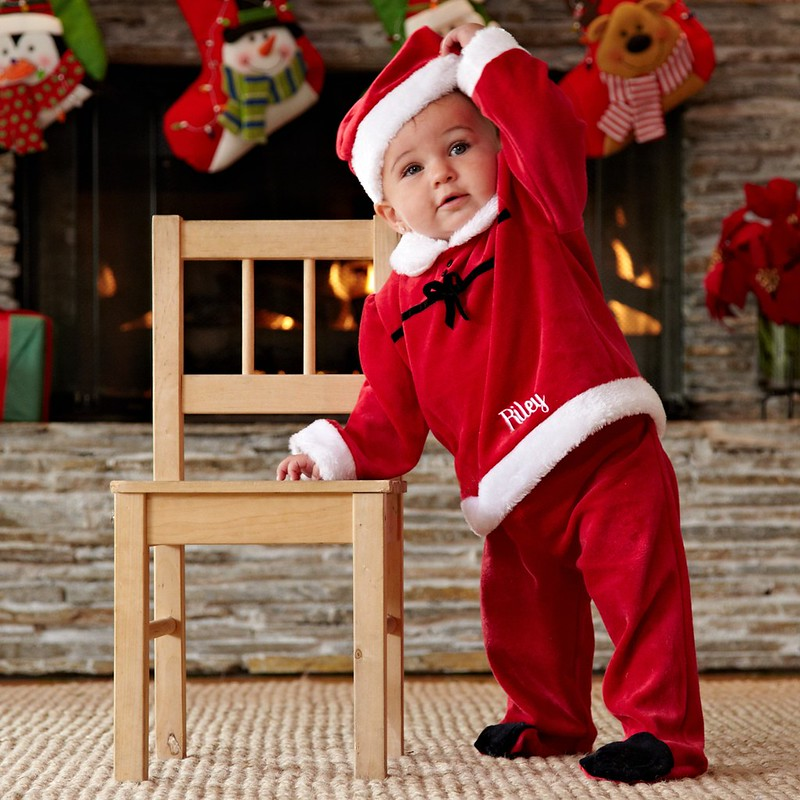 Baby in a personalized Santa costume leaning on a chair in front of the fireplace with stockings hanging in the background