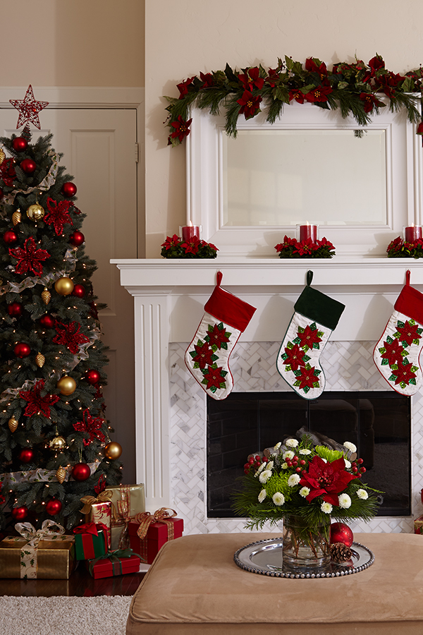 Poinsettia flower centierpieces with candles on mantel over fireplace with stocking hung next to Christmas tree with gifts underneath an ottoman with a holiday floral bouquet on it with poms and mums