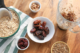 oatmeal dates seeds nuts in bowls with a measuring scoop and a pitcher on a wood table | by PersonalCreations.com