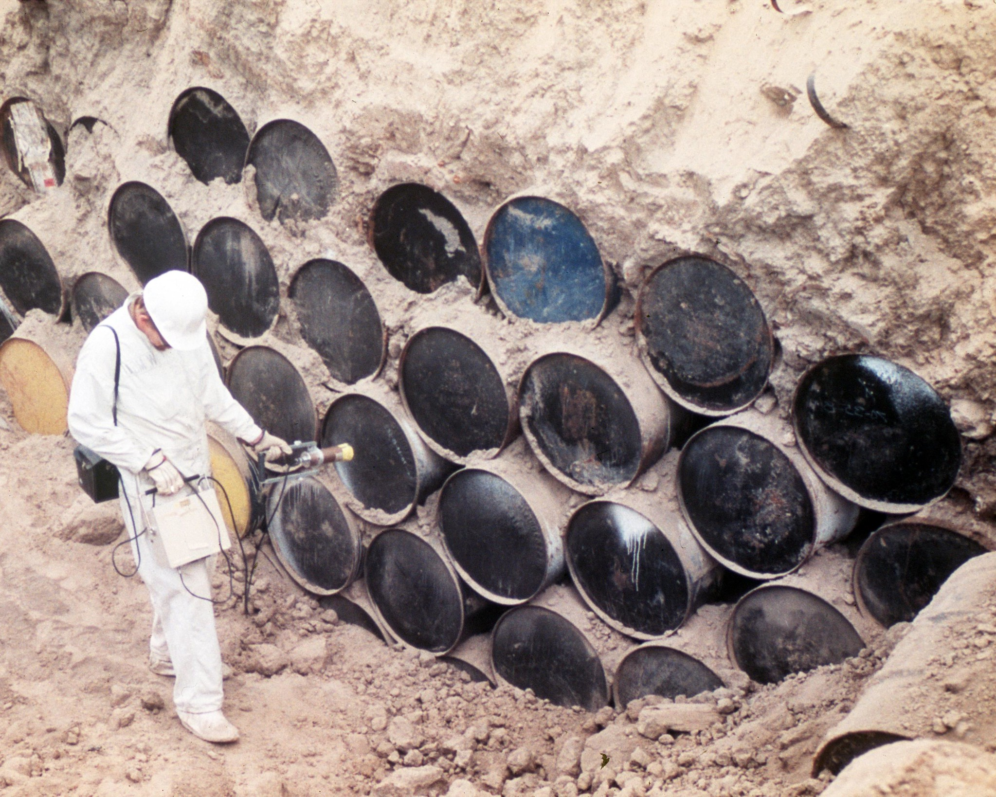 A male-presenting figure in white coveralls with a white hardhat and white gloves holds a geiger counter to the lids of waste storage drums piled and partially buried in what appears to be sand.