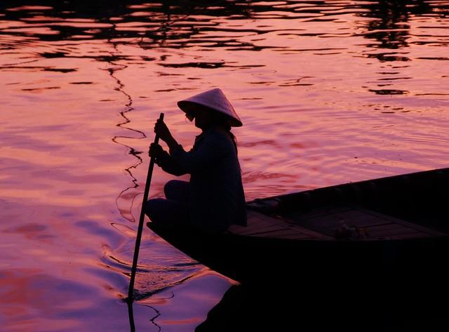 Silueta de una mujer en embarcación vietnamita en Hoi An