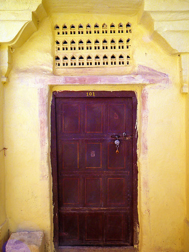 A dark red door and a yellow wall in Jaisalmer, India