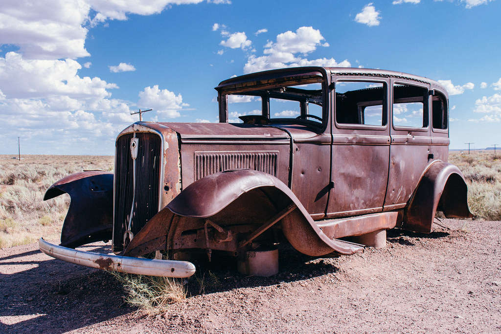 Rusted out body of a 1920s or 1930s era car in the middle of the desert
