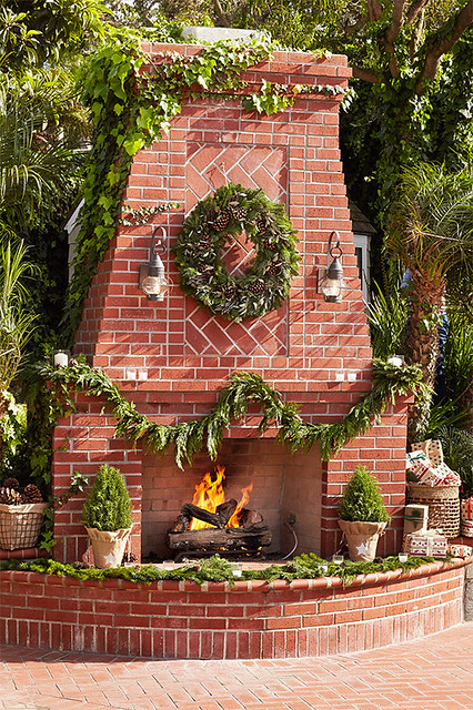 Outside brick fireplace with pine wreath, miniature Christmas trees burning logs
