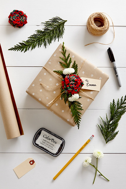 Polka dot delight gift wrapped present with pine clippings a sharpie pen twine and a bow on a white table