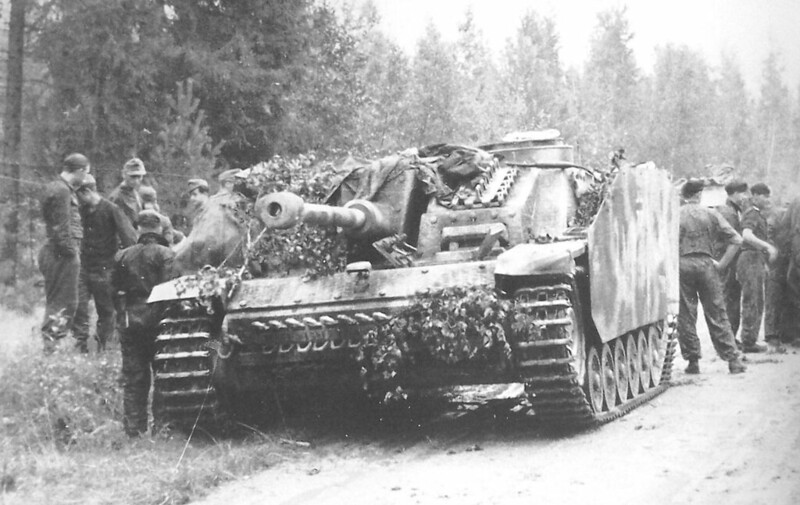 STuG iii G covered in foliage with some infantry