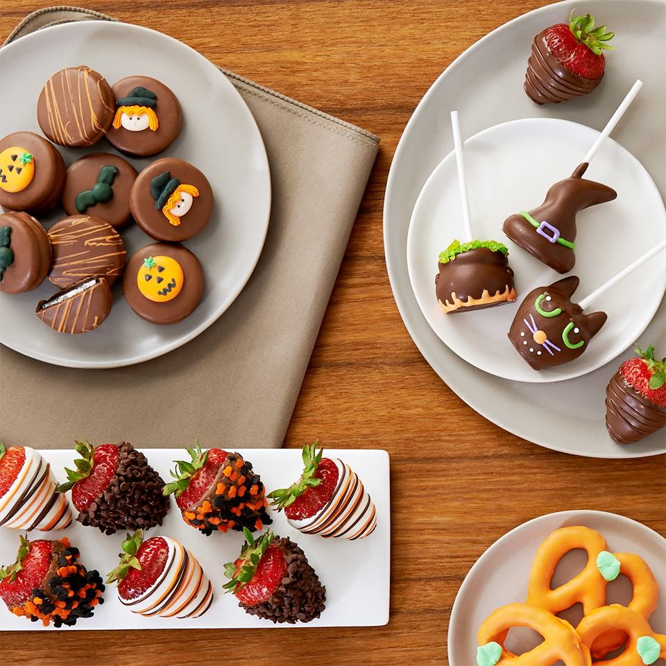 An assortment of Halloween treats including brownie pops shaped like witch hats cats and a cauldron plus chocolate covered Oreos dipped strawberries and pumpkin pretzels on plates on a table