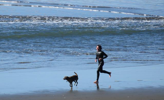 surfer and his dog running at Ocean Beach, San Francisco; January 1, 2015