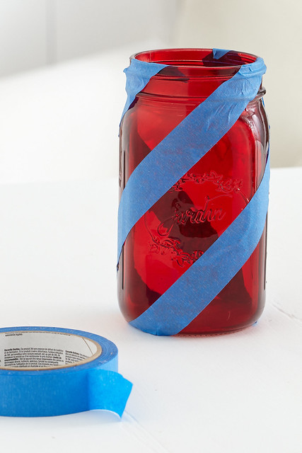 Red glass mason jar with blue tape around it