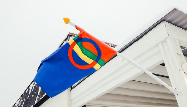 Bandera de los sami (o lapones) ondeando al lado de una de sus cabanias