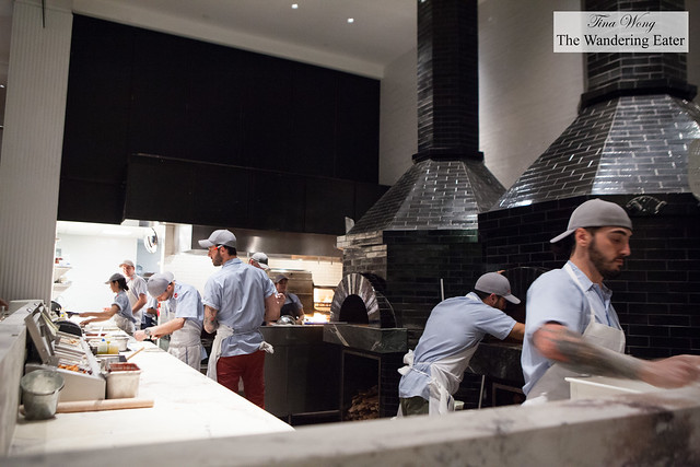 The open kitchen with huge brick wood fire burning ovens
