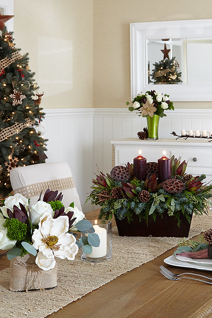 Rustic table setting with pine cone and cutting centerpiece with candles on wood table with decorated Christmas tree and floral bouquet in green glass vase and votives in background