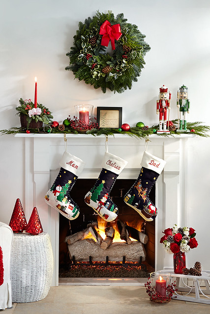 Merry mantel with a wreat and red ribbon, nutcrackers, personalized stockings red roses in a mason jar vase centerpiece with lit candle in front of a fireplace and pine cuttings with ornaments and jingle bells