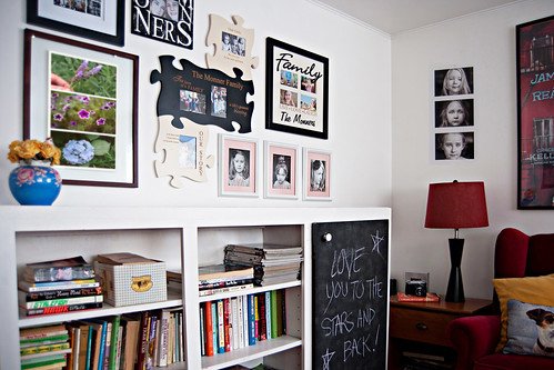 photograph wall gallery in home with photo frames on wall a bookcase and an end table with lamp | by PersonalCreations.com