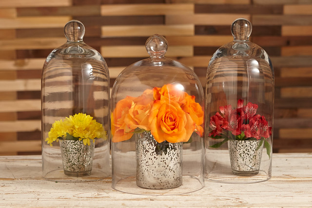 orange roses red alstroemeria Peruvian lilies and yellow viking poms in bell shaped glass on a table