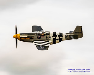 A P-51B MUSTANG AGAINST AN OVERCAST SKY