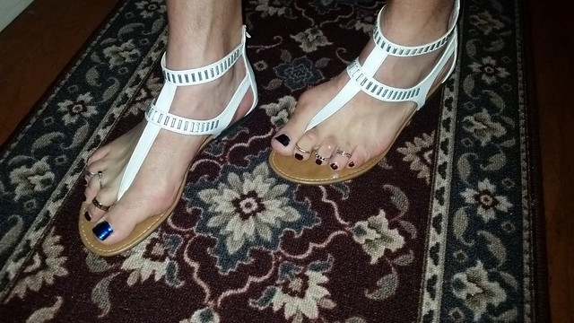 White t-strap sandals with nail polish and toe rings
