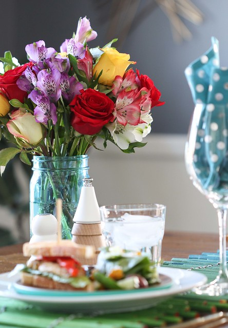 Smiles and Sunshine bouquet of flowers with red, yellow and white roses and purple, pink, and white alstroemeria Peruvian lilies in a blue mason jar glass vase next to a sandwich on a blue plate and a wine glass with a polka dot napkin folded in it