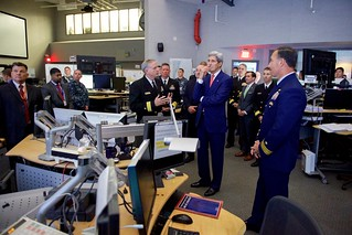 Secretary Kerry Listens to U.S. Navy Rear Admiral Mewbourne as he Delivers a Briefing