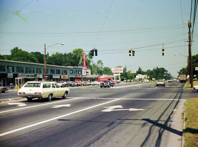 The Boston Post Road looking west from the the very edge of the Connecticut Post Shopping Center parking lot. 1960s and 1970s cars, American Carpet Stores, Dunkin Donuts and a Mobil station. Milford Connecticut. July 1974