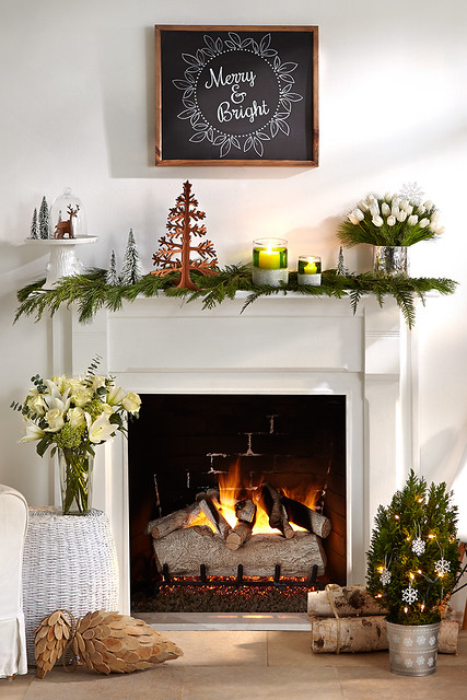 Merry mantel with pine cuttings a Christmas tree decoration white tulps roses and lilies a miniature tree pine cone firewood votive candles in front of a fireplace and a chalkboard hanging on wall