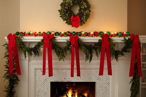 A garland strung across a fireplace mantel with bright red ribbons and a pine wreath with a bow hanging on the wall | by ProFlowers.com