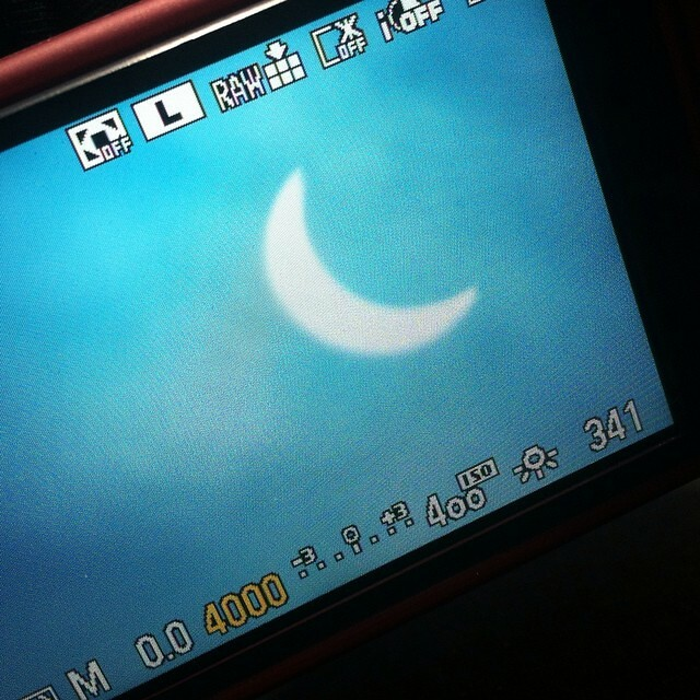 It's getting dark…  #Eclipse as seen thru cloud on the camera screen. 9:25.