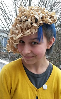 Iris wearing first compostable worm hat made from crocheted coffee filter strips.