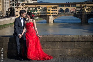A couple pose for wedding photographs with the Ponte Vecchio in the background | by Winniepix