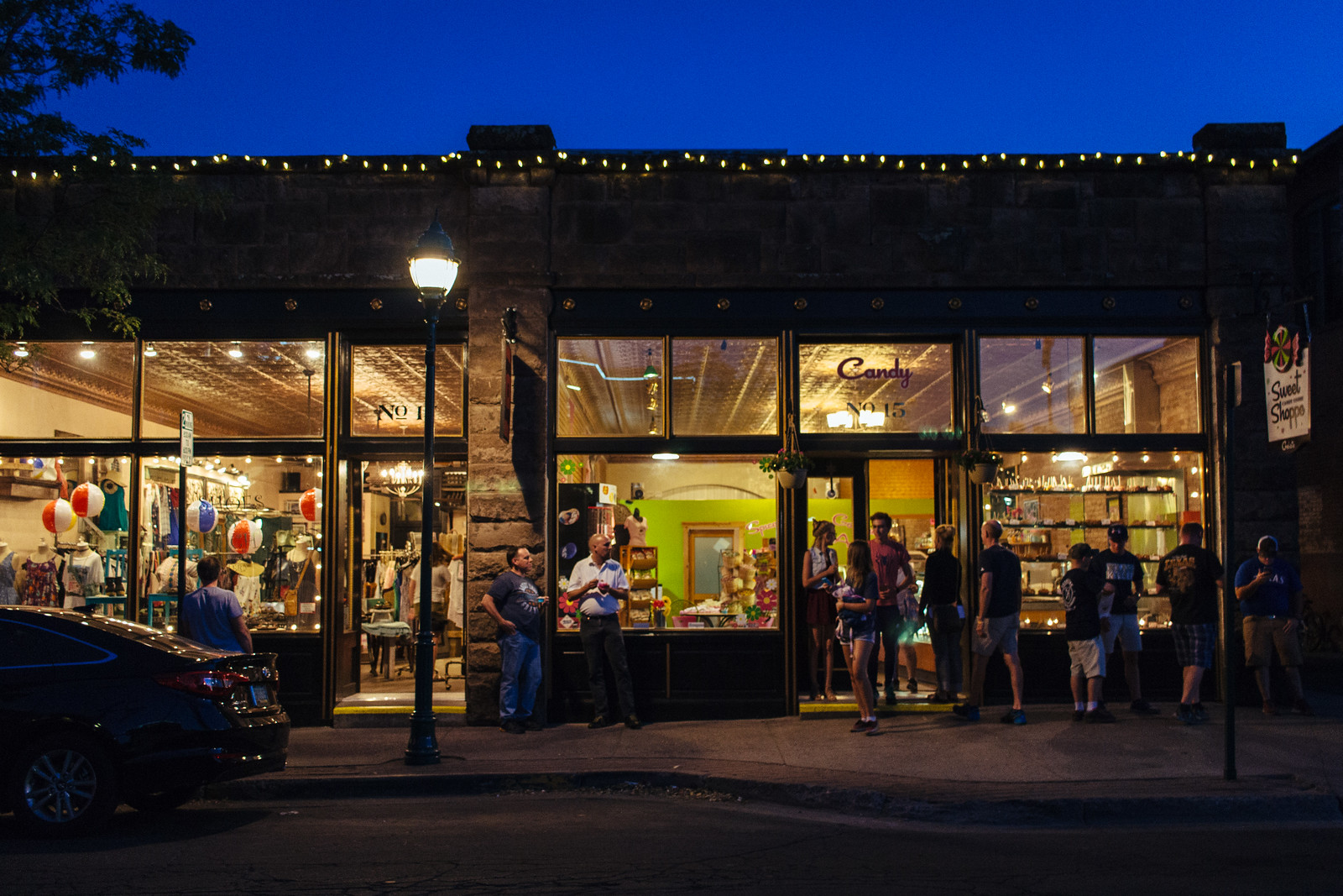 Pedestrians walk in front of a historic storefront at the blue hour in Flagstaff, Arizona