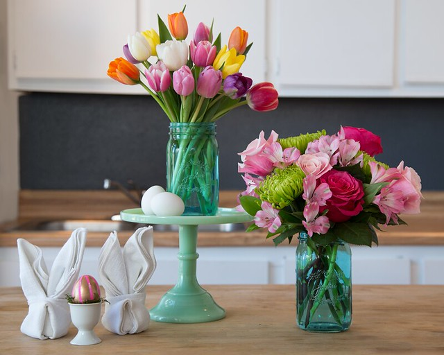 multicolored tulips alstroemeria Peruvian lilies roses spider mums in blue mason jar glass vases with napkins and decorative Easter Egg on counter in kitchen
