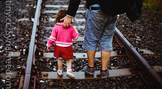 A refugee helps his daughter to run at the railway track after he crossed the Serbian-Hungarian border