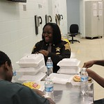 February 18, 2016 - 12:05 - The number of juvenile inmates in the Marion County Jail usually hovers around 40, but the command staff of the Jail understands that this population of inmates are still developing mentally and still need the care and attention of adults. Jail Commander James Martin and Major Tanesha Crear ordered a special lunch of cheeseburgers and chips in early 2016, and sat down with the juveniles to listen to what they have to say, and to also inform them of some upcoming programs based on good behavior. This photo of Major Tanesha Crear laughing with these young inmates really captures the heart of our Sheriff's Deputies in the Jail Division. Credit: Katie Carlson, Marion County Sheriff's Office