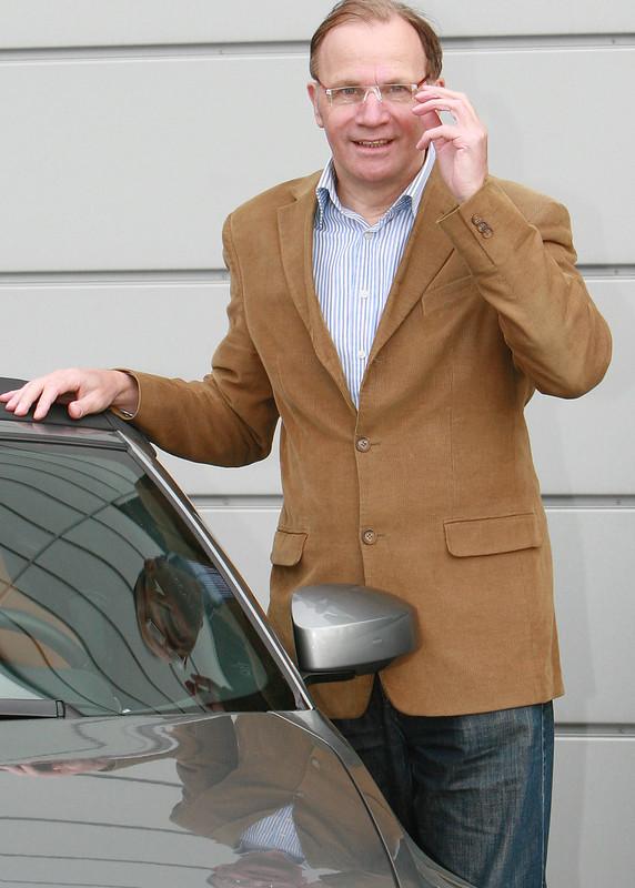 Geschäfstmann mit Handy am Auto