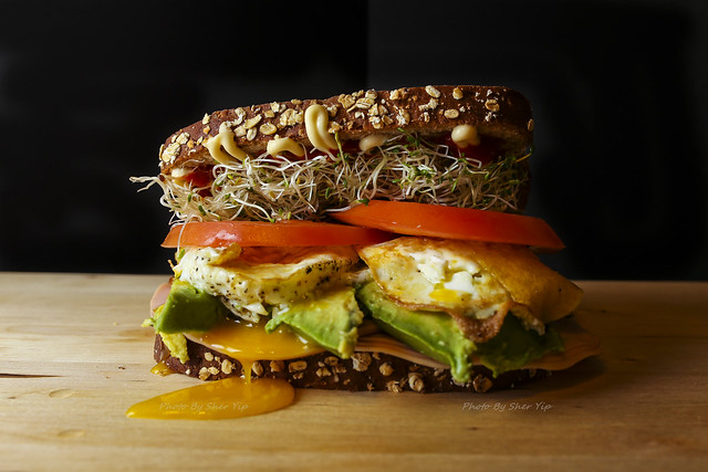 Homemade Spring sandwich! 12 grain bread, Sprouts, Tomato, Overeasy Egg, Avocado, Smoked Turkey, Sriracha, and Kewpie