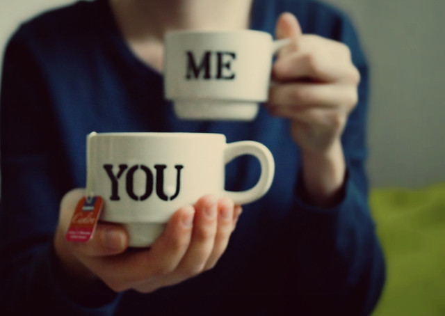 A person holding two mugs of tea, one that says 'me' they're holding to their chest, another says 'you' they're offering to the viewer