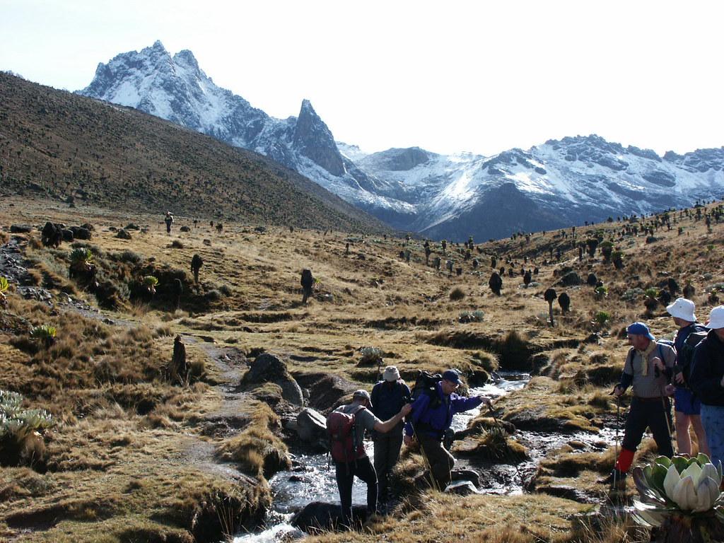 Crossing a stream in the Teleki Valley, with Mount Kenya behind.