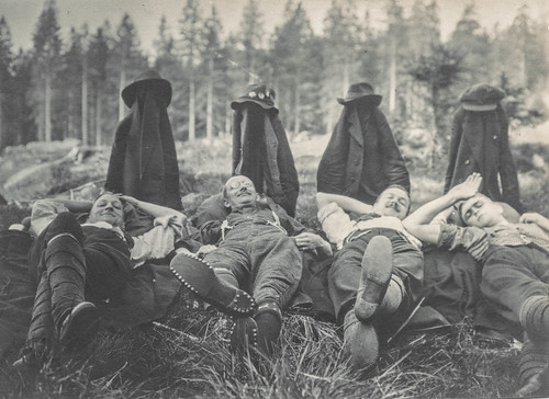 Men lying on the ground with propped up jackets