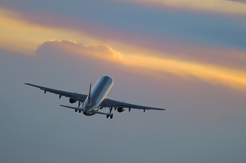 Airplane taking off in the sunet