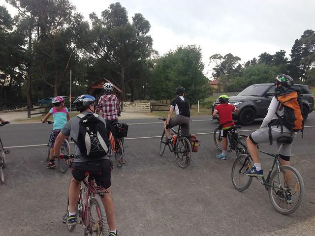 Cyclists wait to cross Warburton Highway, Wandin