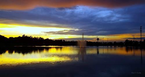 sunsetinparadise sunset reedcanalpark reedcanallake fountain lake water silhouettes trees reflecrtions sky clouds dramaticsky colorful southdaytonaflorida