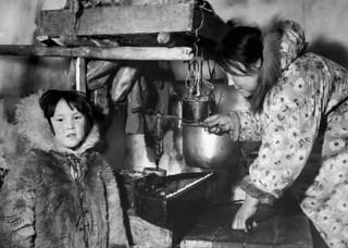 Inuit woman tending the qulliq (seal-oil lamp) inside an igloo, Nunavut / Une femme inuite s'occupe d'un qulliq (lampe alimentée à l'huile de phoque) dans un igloo, au Nunavut