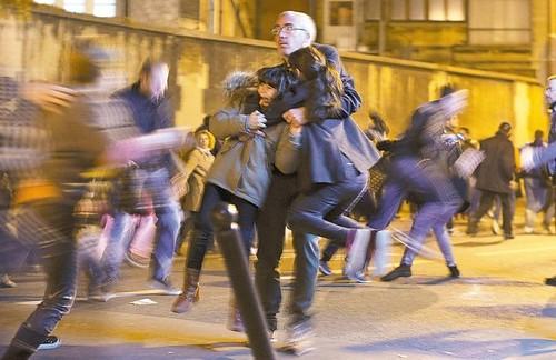 圖04  巴黎恐攻中法國民眾聽到爆炸聲,一名男子摟著兩名孩子拔腿就跑。
