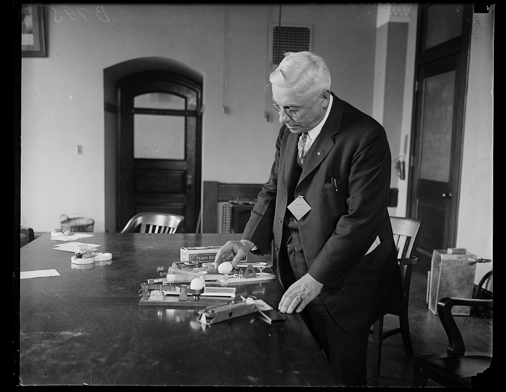 Identified! [Man with variety of egg scales used for grading eggs] (LOC)