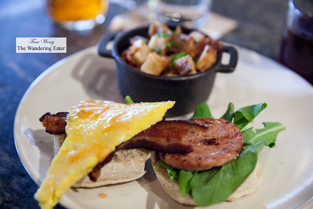 English muffin, bacon, breakfast sausage, arugula, Empire State South hot sauce, scrambled egg with a side of hash