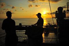 Sailors aboard USS Blue Ridge (LCC 19) watch the sunrise as the ship arrives in Singapore for a port visit. (U.S. Navy/MC3 Liz Dunagan)