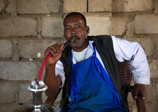 Beja man smoking water pipe, Red Sea State, Suakin, Sudan