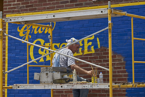 A master sign painter painting a local advertisment.